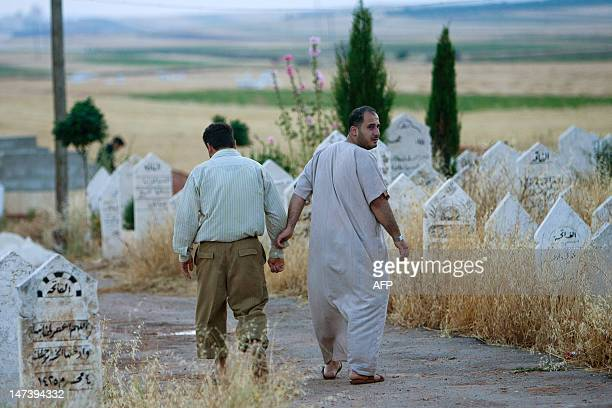 Syrians men walk through a cemetery in Tal Refaat village near Aleppo during the burial of 70yearold Amina Ahmed Kabso who was killed in the latest...