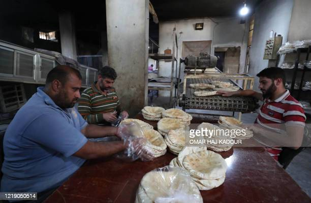 Syrians pack bread at a bakery in the town of Binnish in the country's northwestern Idlib province on June 9, 2020. - Syrians held a third day of...