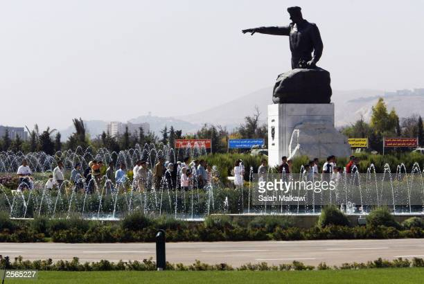 """Syrians pass near a statue of late Syrian Preisdent Hafez al-Assad at an exhibition about the 1973 Arab-Israaeli war at the """"6 October Museum"""" on..."""