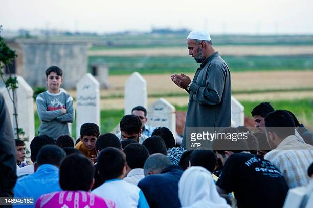 Syrians pray at a cemetery in Tal Refaat village near Aleppo during the burial of 70yearold Amina Ahmed Kabso who was killed in the latest spate of...
