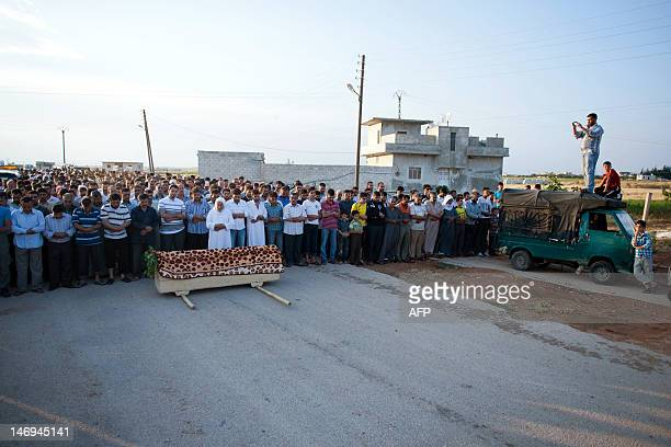 Syrians pray at a cemetery in Tal Refaat village near Aleppo over the coffin of 70yearold Amina Ahmed Kabso who was killed in the latest spate of...