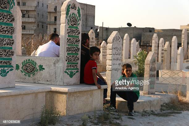 Syrians pray for their relatives on the first day of Eid alFitr at a cemetery in Aleppo Syria on July 17 2015 Muslims around the world celebrate Eid...