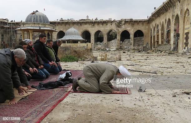 TOPSHOT Syrians pray in the ancient Umayyad mosque in the old city of Aleppo on December 17 as civilians are allowed access to some neighbourhoods...