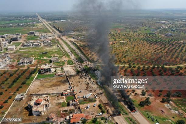 Syrians protest and burn tyres in an attempt to block traffic on the M4 highway, which links the northern Syrian provinces of Aleppo and Latakia,...