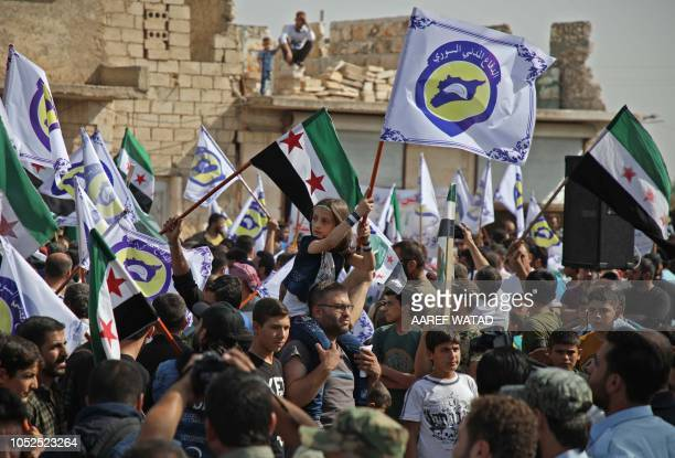 Syrians raise opposition flags and flags bearing the emblem of the Syrian Civil Defence during a gathering in Anjara in the western countryside of...