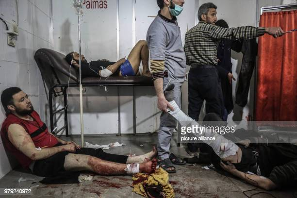Syrians receive first aid in a makeshift hospital after being injured during air strikes by forces loyal to Syrian President Assad in Kafr Batna a...