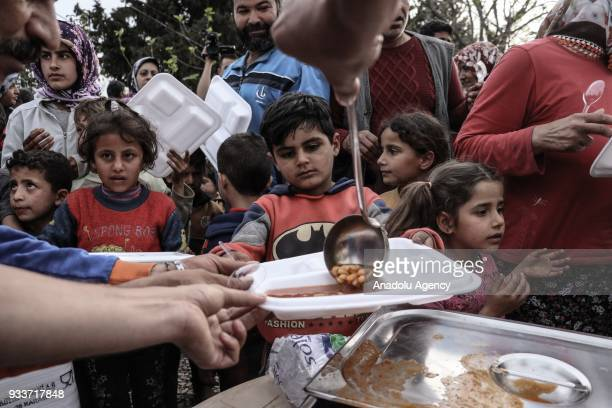Syrians receive food aid from Disaster and Emergency Management Presidency in Jinderes on March 18 2018 after the town was cleared from...