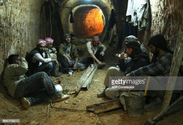 TOPSHOT Syrians rest as they dig a tunnel under the rebelheld area of Jobar to take cover from shelling on October 25 2017 / AFP PHOTO / Ammar...