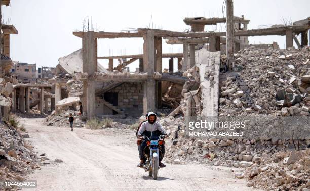 Syrians ride a bicycle past destroyed buildings in an opposition-held neighbourhood of the southern city of Daraa on October 2, 2018.