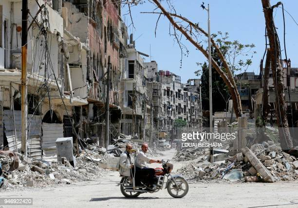 TOPSHOT Syrians ride a motorbike along a destroyed street in Douma on the outskirts of Damascus on April 16 2018 during an organised media tour after...