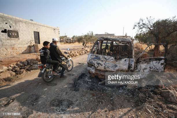 TOPSHOT Syrians ride a motorcycle past a burnt vehicle near the site where a helicopter gunfire reportedly killed nine people near the northwestern...