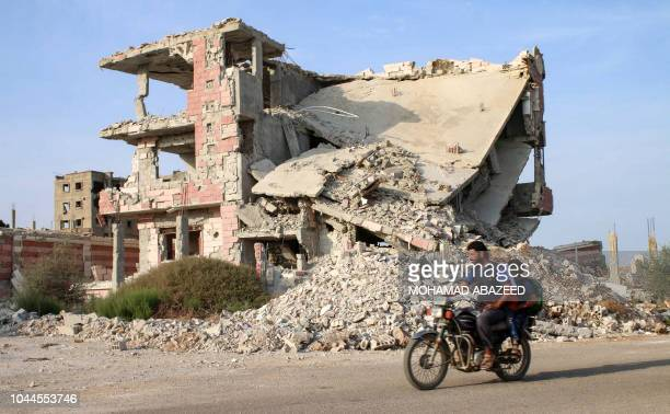 Syrians ride a motorcycle past destroyed buildings in an opposition-held neighbourhood of the southern city of Daraa on October 2, 2018.