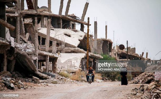 Syrians ride a motorcycle past destroyed buildings in an opposition-held neighbourhood of the southern city of Daraa on October 1, 2018.