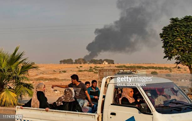 TOPSHOT Syrians ride a pickup truck past smoke as Arab and Kurdish civilians flee following Turkish bombardment on Syria's northeastern town of Ras...