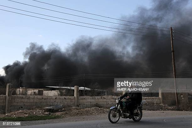 Syrians ride their motorbike as smoke billows in the background following reported air strikes on the rebelheld village of alChifouniya on the...