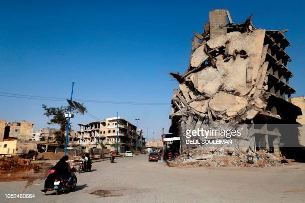 TOPSHOT Syrians ride their motorcycles past a damaged building in the Syrian city of Raqa on October 18 2018 A year after a USbacked alliance of...