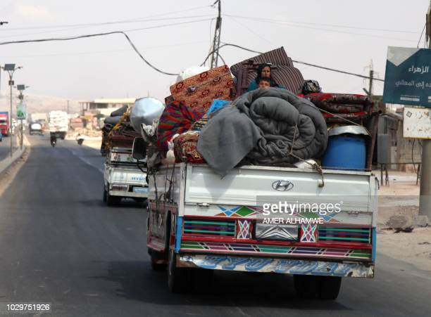 Syrians ride with their belongings in trucks as they head to safer areas in the town of Khan Sheikhun on the southern edges of the rebelheld Idlib...