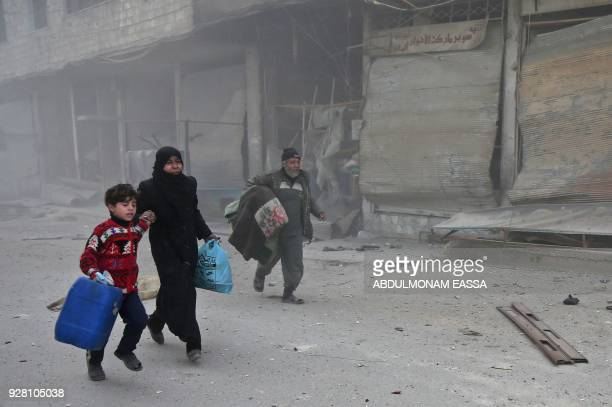Syrians run for cover in Hamouria during Syrian government shelling on rebelheld areas in the Eastern Ghouta region on the outskirts of the capital...