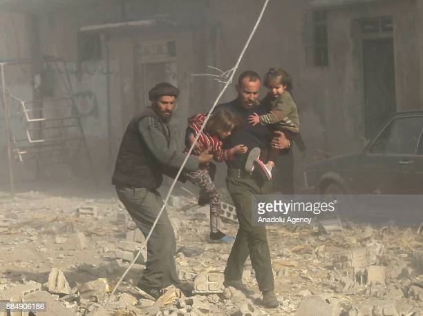 Syrians run with their children following the Assad regime's air strikes over residential areas in the deescalation zone in the Eastern Ghouta region...