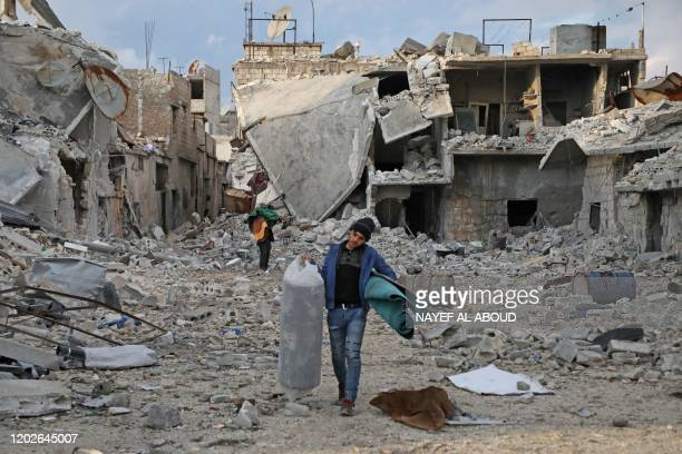 Syrians salvage some of their belongings from the rubble of houses as they prepare to flee the town of Atareb in the rebel-held western countryside...