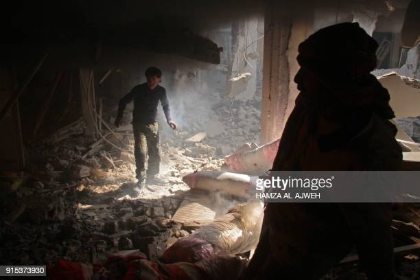 TOPSHOT Syrians search for survivors following regime air strikes on the rebelheld besieged town of Douma in the eastern Ghouta region on the...