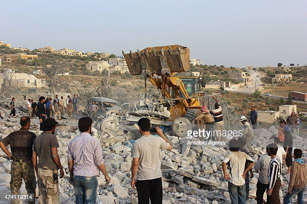 Syrians search for survivors in the rubble of buildings destroyed during the airstrikes of Syrian regime forces on the headquarters of AlNusra Front...