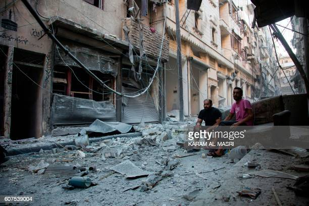 TOPSHOT Syrians sit and look at the rubble following an air strike in Aleppo's rebelcontrolled neighbourhood of Karm alJabal on September 18 2016...