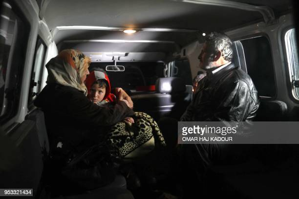 TOPSHOT Syrians sit in the back of a vehicle in AlSuwaghiyah in Idlib province as a convoy transporting civilians from the besieged Shiite areas of...