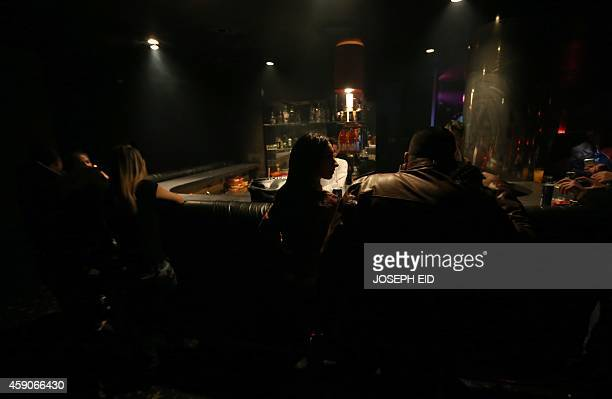 Syrians sit on the bar at a night club in the governmentcontrolled part of the northern city of Aleppo on November 15 2014 AFP PHOTO/JOSEPH EID