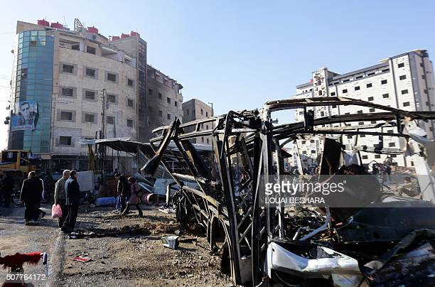 Syrians stand in front of the wreckage of vehicles at the site of suicide bombings in the area of a revered Shiite shrine in the town of Sayyida...
