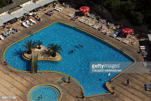 Syrians swim and sunbathe next to a pool at alShahba hotel in Aleppo's governmentheld Meridian neighborhood on September 15 2016 Violence broke out...