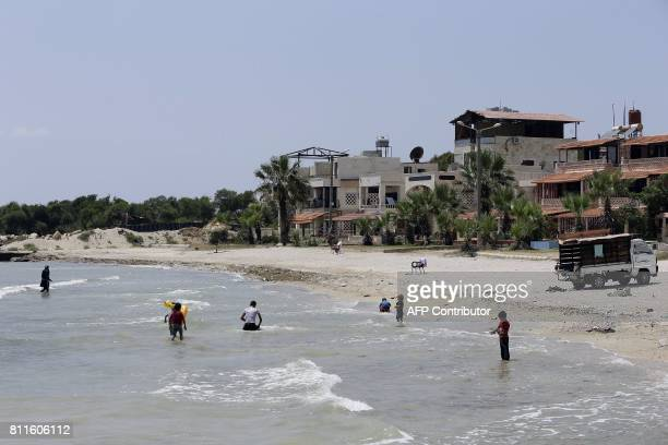 Syrians take a dip in the Mediterranean Sea in the northwestern city of Latakia on July 7 2017 A popular seaside resort largely untouched by the...