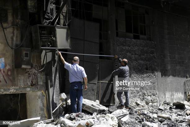 Syrians take measures of the entrance of their factory as they prepare to renovate it in Aleppo's Kallase industrial neighbourhood on July 5 2017 Six...