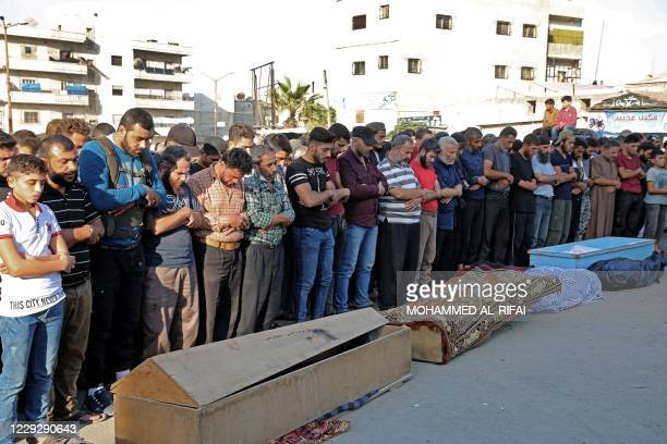 Syrians take part in the funeral of 10 fighters with the Turkey-backed Faylaq al-Sham rebel faction in Syria, in the northwestern city of Idlib, on...