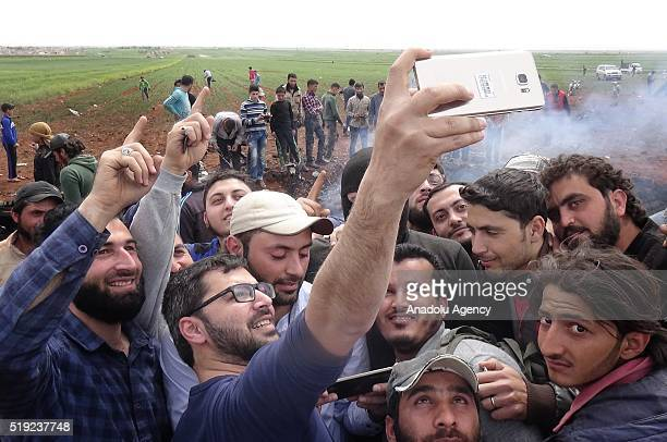 Syrians take selfie in front of a wreckage of a Syrian Regime Forces' warplane after it has been shot down by the opposition forces in Aleppo's Ays...