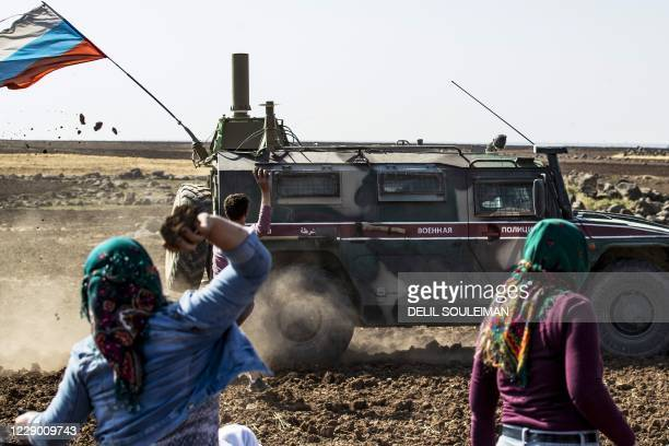 Syrians throw rocks at a Russian Military Convoy near the village of Ein Diwar in Syria's northeastern Hasakeh province on October 11 in an attempt...