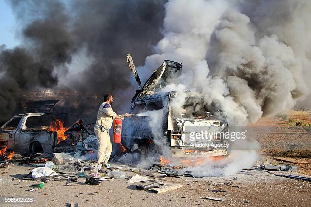 Syrians try to extinguish fire after war crafts belonging to the Assad Regime forces carried out an airstrike over vehicles carrying civilians out of...