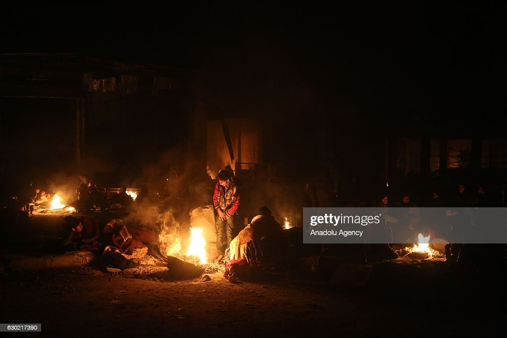 Syrians try to get warm as they wait to be evacuated from the east part of Aleppo that had been under siege by Assad Regime forces and its supporter foreign terrorist groups at a crossing point at Amiriyah district of Aleppo in Syria on December 19, 2016.