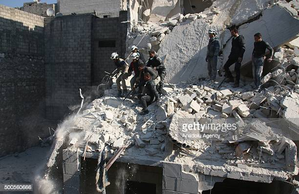 Syrians try to rescue people who are trapped under the rubble of a collapsed building after the warcrafts belonging to the Russian army carried out...