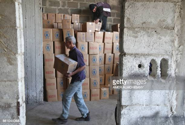 Syrians unload aid packages provided by the International Committee of the Red Cross in a joint operation with the UN in the alNashabia town in the...
