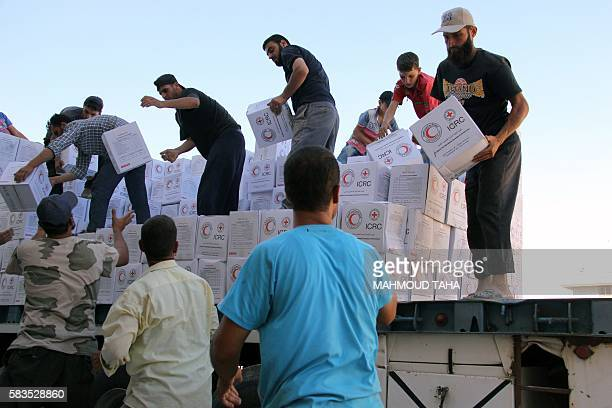 Syrians unload boxes after a 48truck convoy from the ICRC SARC and UN entered the Syrian rebelheld town of Talbiseh a besieged area in northern rural...