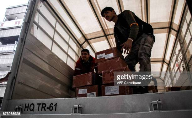 Syrians unload humanitarian relief packages provided by the International Committee of the Red Cross in a joint operation with the UN in the town of...