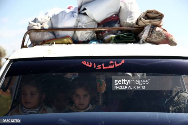 TOPSHOT Syrians wait at a check point in the village of Anab ahead of crossing to the Turkishbacked Syrian rebels side on March 17 as civilians flee...