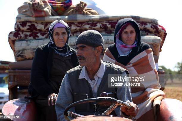 Syrians wait at a check point in the village of Anab ahead of crossing to the Turkishbacked Syrian rebels side on March 17 as civilians flee the city...
