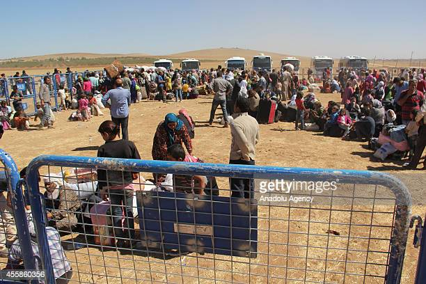 Syrians wait at the coordination center set up by the Turkish Disaster and Emergency Management Agency on TurkishSyrian border after fleeing from the...