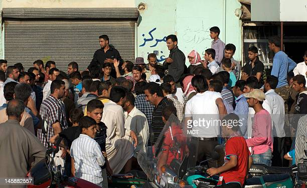 Syrians wait for cooking gas being distributed by the Free Syrian Army in Qalaat Al Mudiq on June 4 2012Throughout northern syria the FSA has carved...