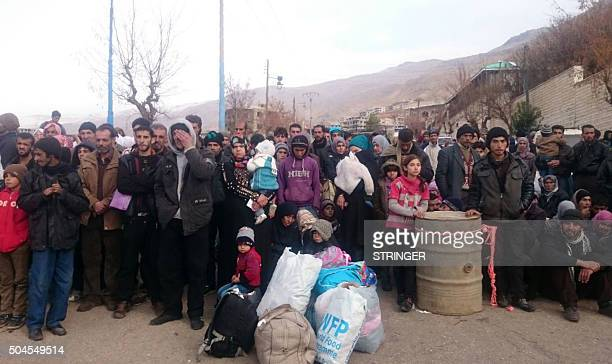 Syrians wait for the arrival of an aid convoy on January 11 2016 in the besieged town of Madaya as part of a landmark sixmonth deal reached in...