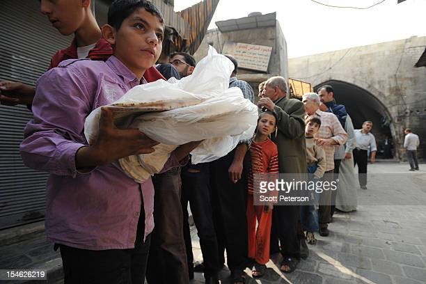 Syrians wait in line to buy bread from a rebel delivery after three months of intense government fighting against rebels of the Free Syrian Army on...