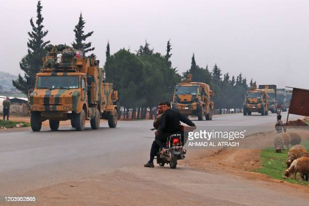 Syrians wait to cross an intersection as a Turkish military convoy drives past the village of Kafr Yahmul north of Idlib in northwestern Syria on...