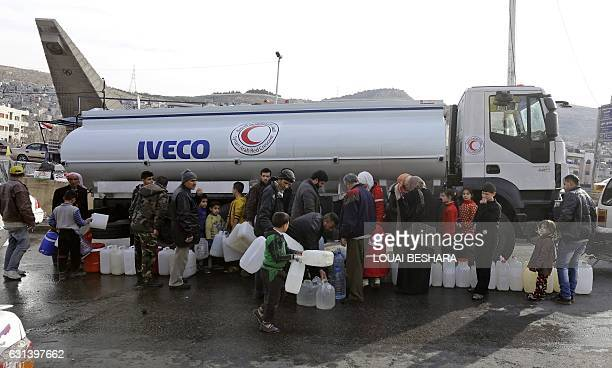 Syrians wait to fill plastic containers with water provided by the Syrian Arab Red Crescent in the capital Damascus on January 10 2017 Millions of...